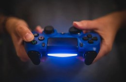 This shows a pair of hands holding a blue PS4 controller
