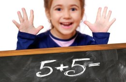 This shows a child with a chalk board full of numbers