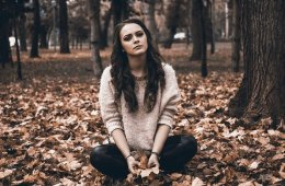 This shows a sad looking woman sitting in a forest with bare trees and leaves on the ground