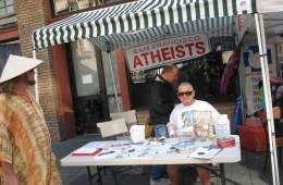 This shows a person at an atheist booth