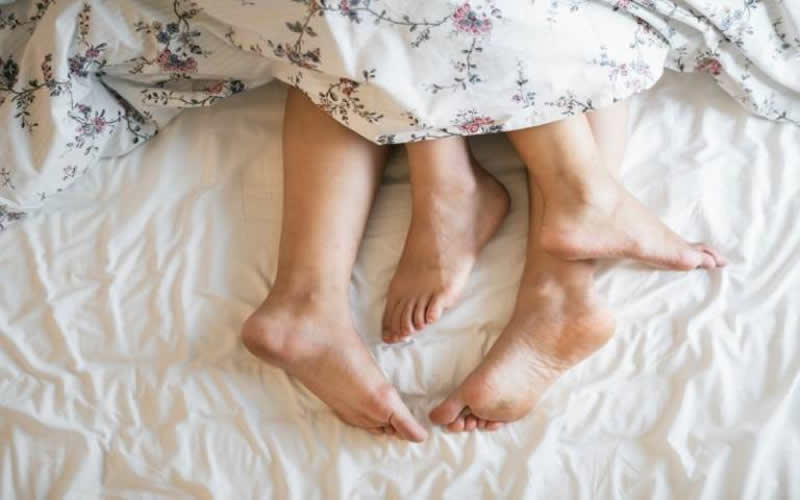This shows a couple's feet sticking out of blankets