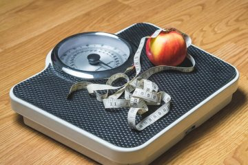 This shows a scales, tape measure and an apple