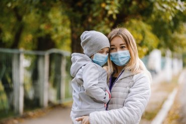 This shows a woman and child in surgical masks