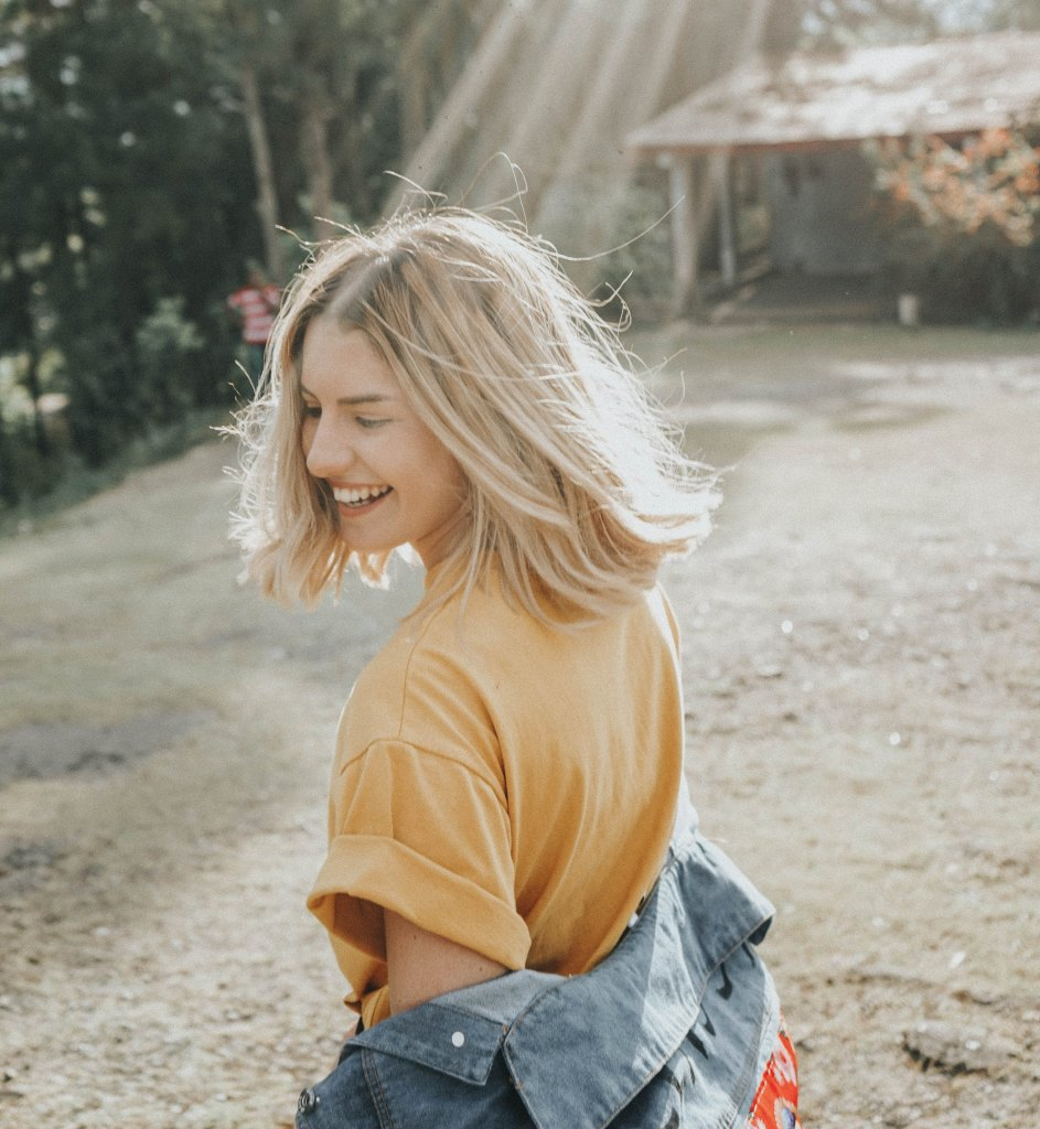 Happy woman in the sunshine. By Gian Cescon on unsplash