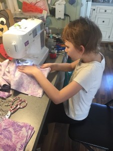 Hannah, 9 years old and first-year 4-H member, sews a face mask. Photo by Laura Wells.