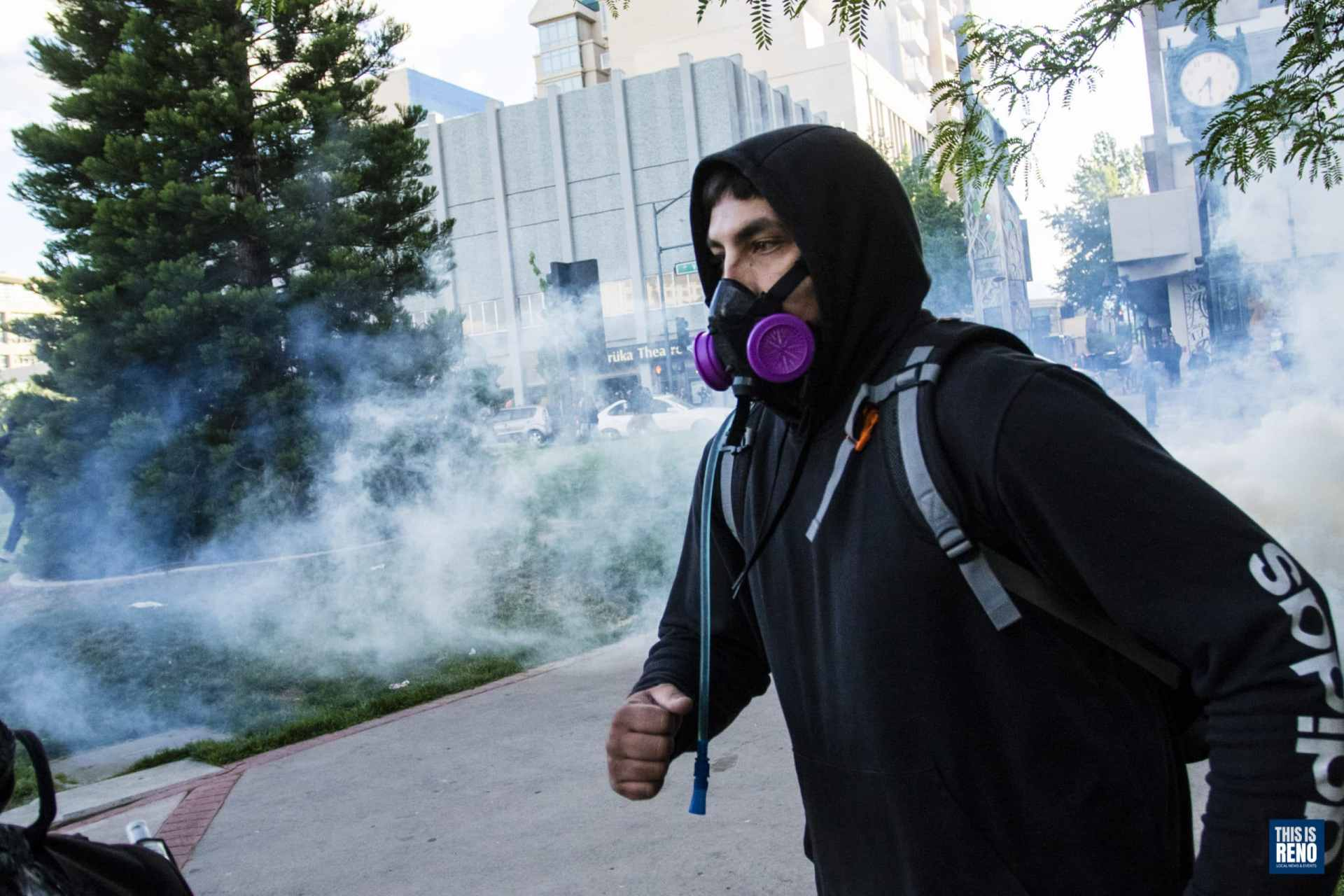 A protester flees tear gas in downtown Reno during riots after a Black Lives Matter protest. Image: Ty O'Neil