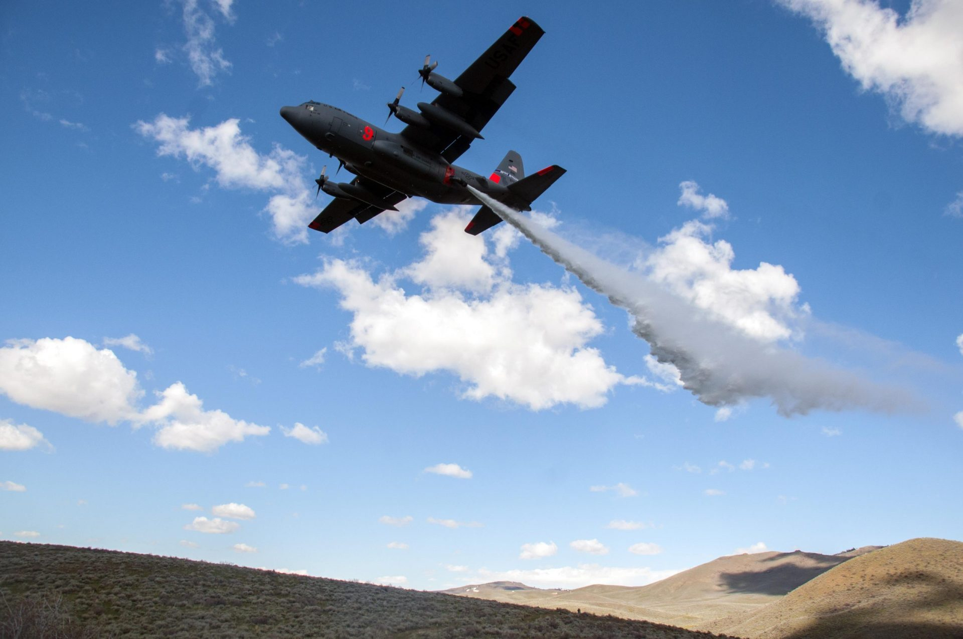 A C-130 with the 152nd Airlift Wing, Nevada Air National Guard, drops water in the mountains east of Boise, Idaho as part of the annual Modular Airborne Fire Fighting System training and certification, April 21, 2017.