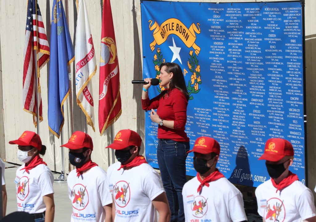 """Standing in front of a Nevada flag with the names of those from the Silver State who were killed in Vietnam, singer Kimberly Dixon leads the audience in """"God Bless America"""" at the conclusion of the National Vietnam War Veterans Day. Members of the Devils Pups line up in front. Steve Ranson / LVN"""
