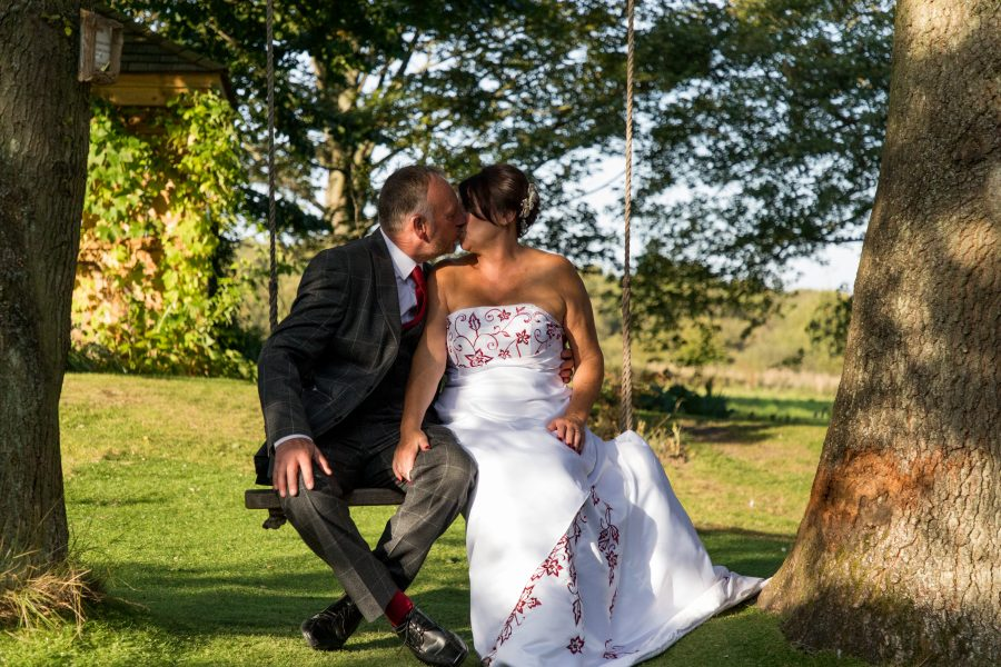 bride and groom kiss on swing in garden