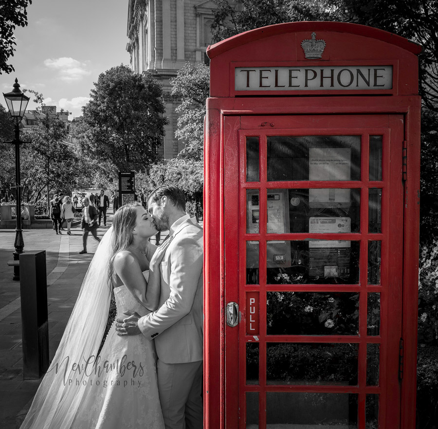 Bride and groom kiss whilst leaning on a red phone box