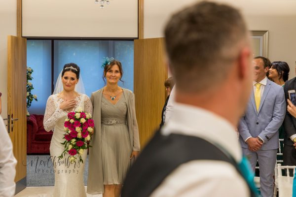 bride and mother walking down the isle with groom looking back