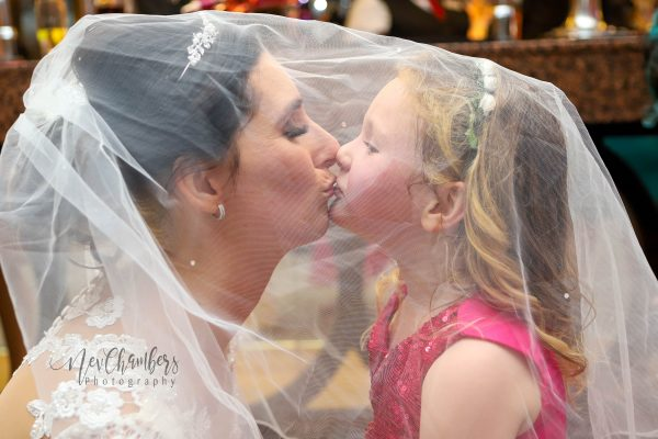 veil, bride and daughter kissing under veil