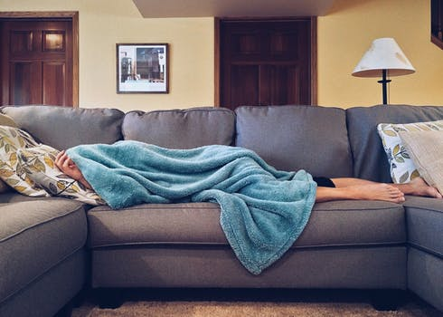 Woman lying under a blanket - stressed out mom.