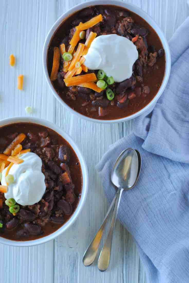 two bowls of chili and spoons