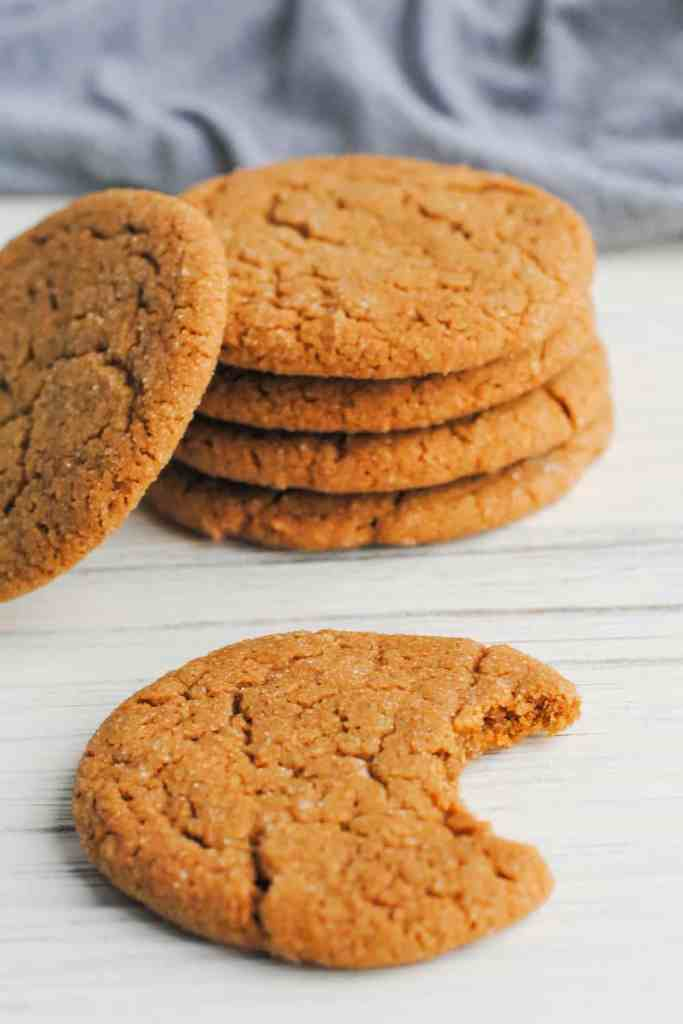 stack of ginger cookies with one to the side and one in front with a bite taken