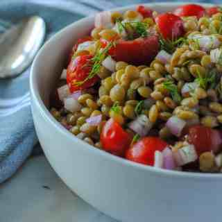 bowl of lentil salad made with tomatoes and dill