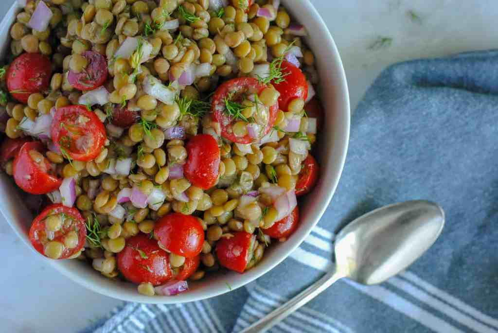lentil salad with tomatoes and dill with gray cloth and spoon