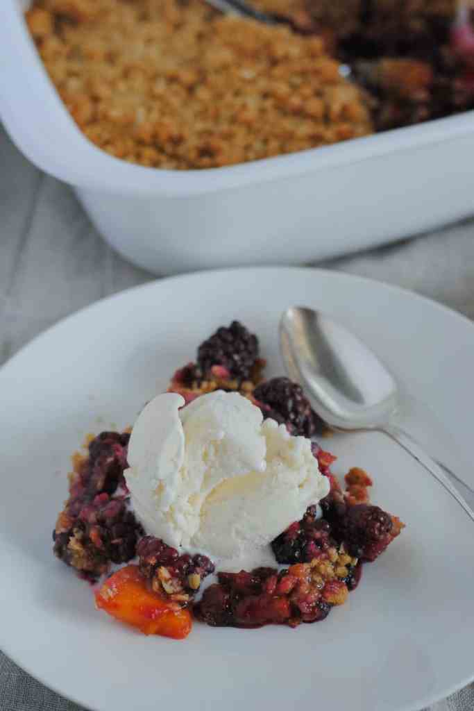 Summer fruit crisp of blackberries, peaches, and plums topped with vanilla ice cream