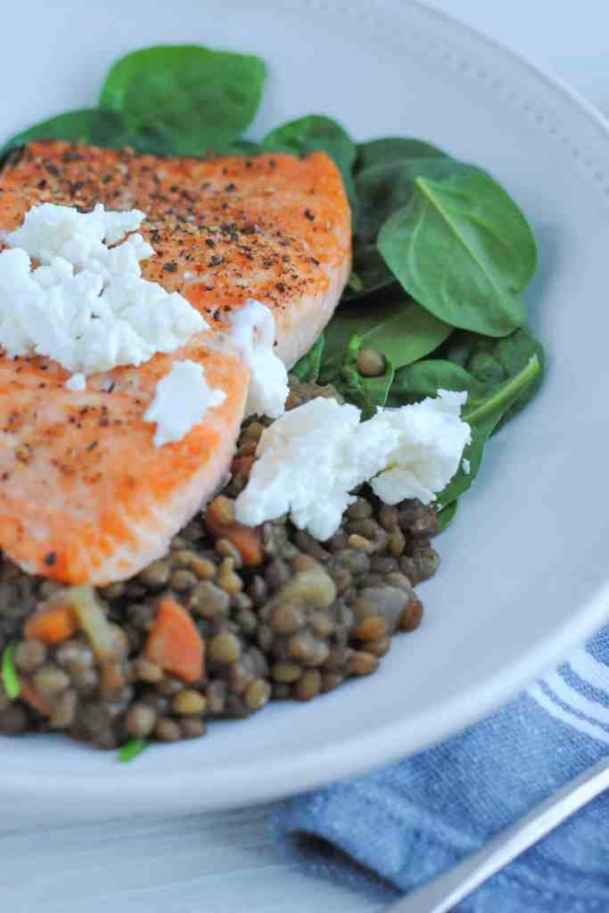 plate of lentils and spinach with salmon topped with goat cheese