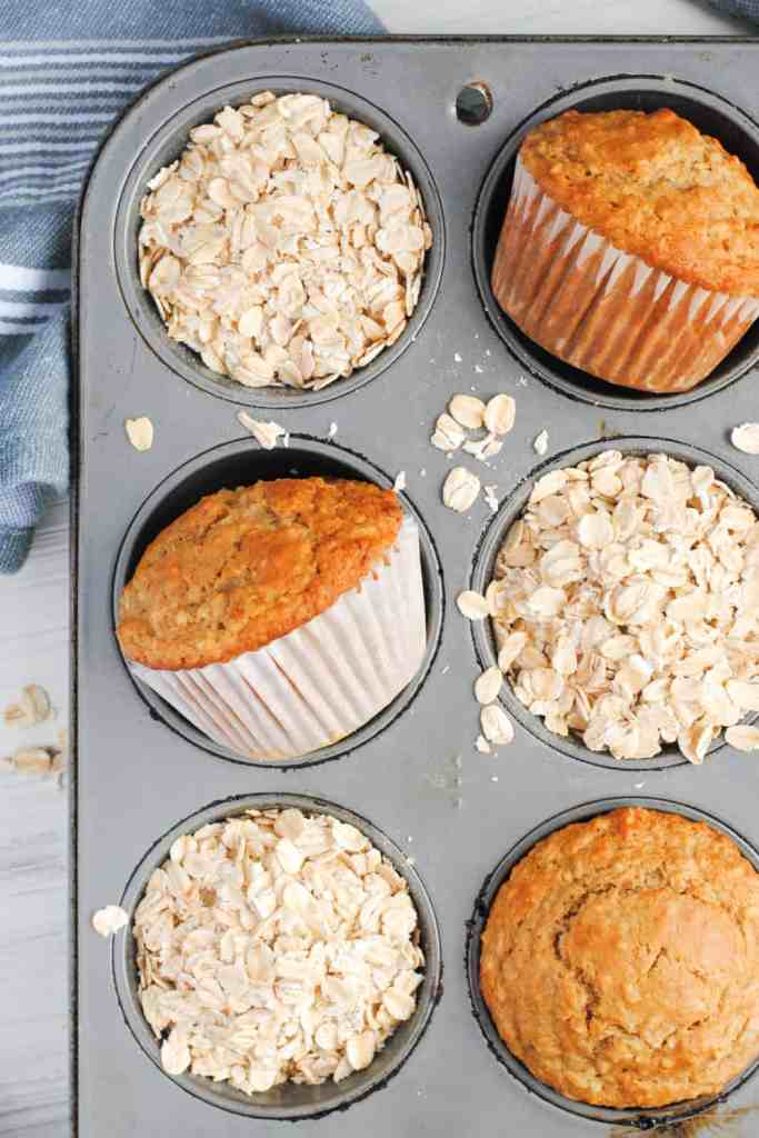 healthy cinnamon oatmeal muffins in a muffin tin with oats