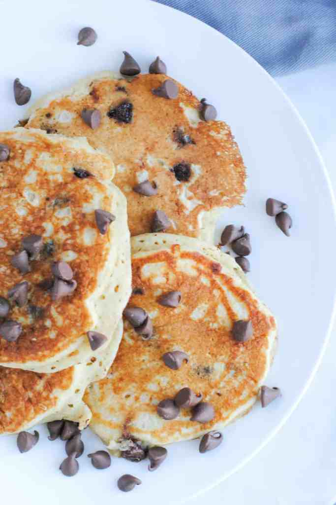 four buttermilk pancakes topped with chocolate chips on a white plate