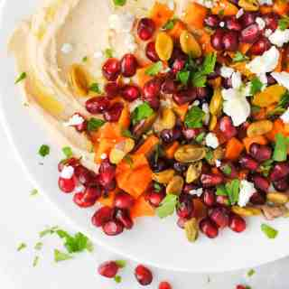 hummus topped with roasted sweet potato, pomegranate seeds, feta, pistachios, mint and parsley with a drizzle of olive oil on a white plate