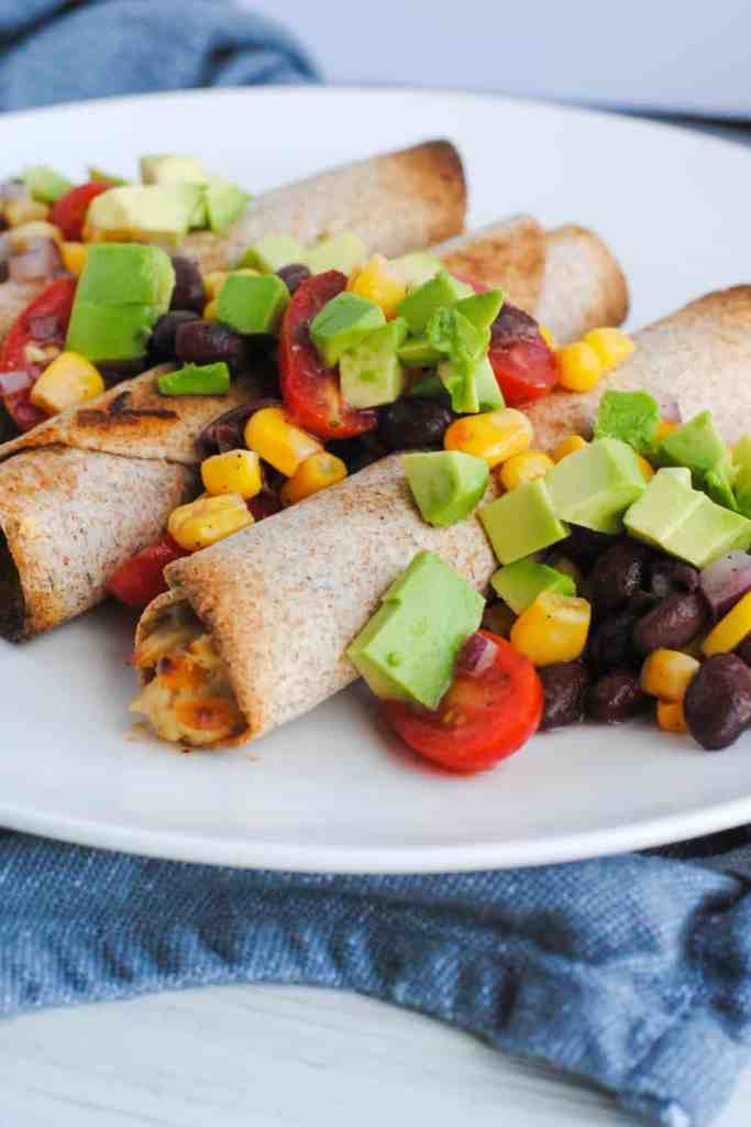 baked chicken taquitos with avocado, corn, black bean, and tomatoes