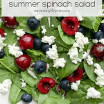 white bowl filled with spinach salad, and topped with cherries, blueberries, goat cheese, and red onion with text overlay red, white & blue summer spinach salad neveranythyme.com