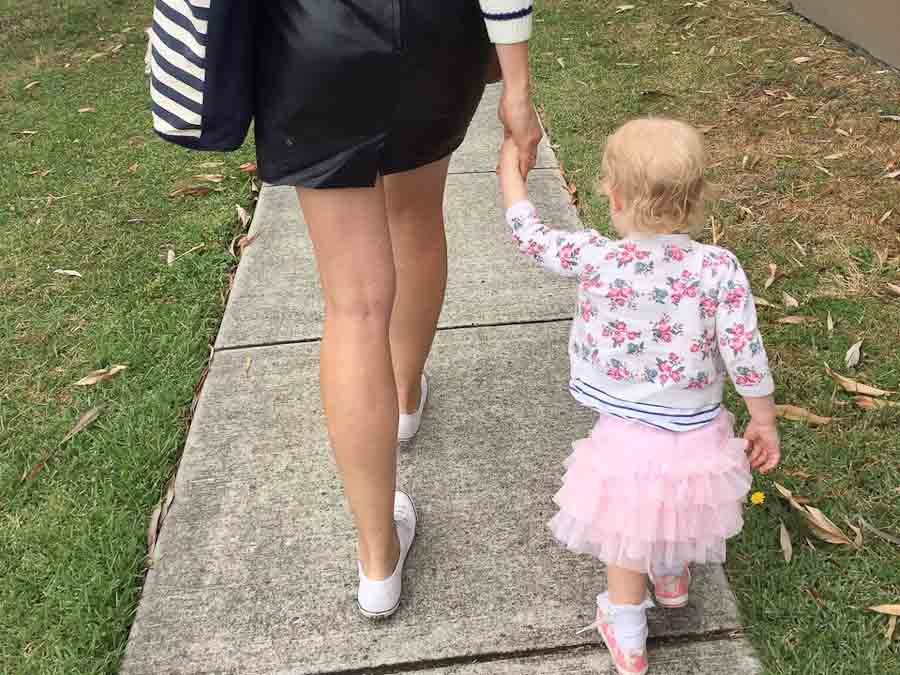 Mum and daughter walking along holding hands