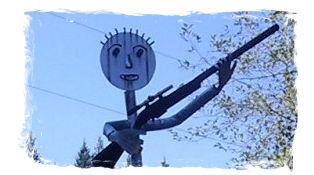welded statue art holding rifle outside gun club