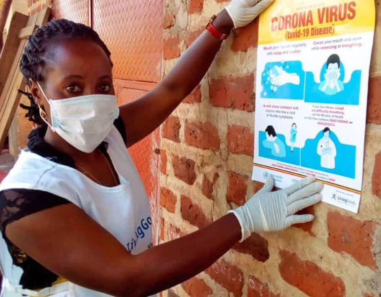 Living Goods Community Health Care worker putting up poster with tips to prevent spread of Coronavirus