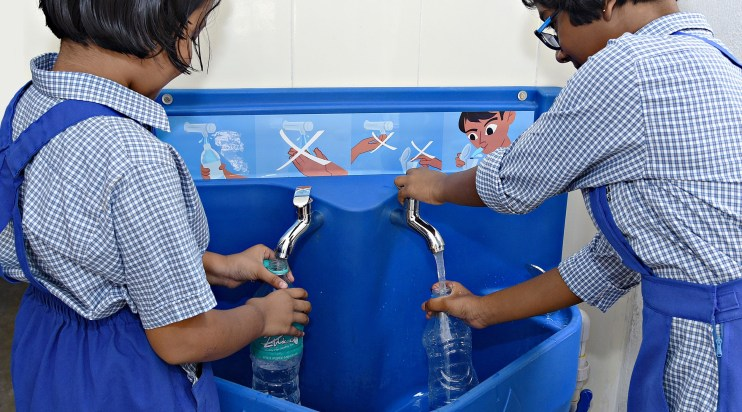 Two school girls in India washing hands at Splash station