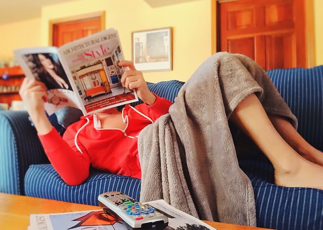 Woman reclining on couch holding magazine.