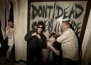 "Norman Reedus, Chandler Riggs & Greg Nicotero pose within the ""Walking Dead: Dead Inside"" maze."