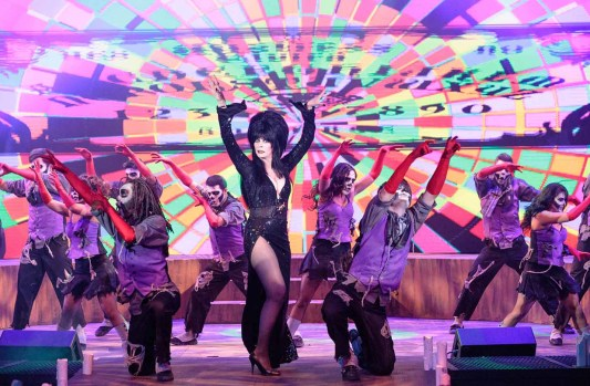 Elvira puts on a colorful Vegas-style song-and-dance show, laced with her signature risque humor.
