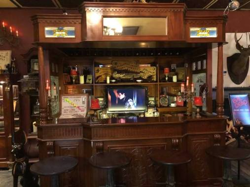 A video clip from Evil Dead plays on a loop behind the bar.