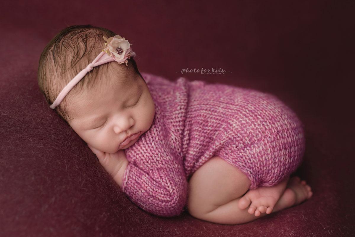 New born girl in pink dress sleeps during a new born workshop by Nicoleta Raftu