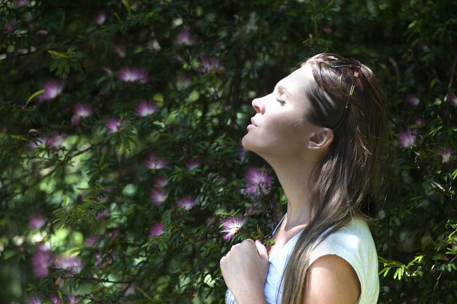 Woman with her eyes closed looking up at the sky with purple and green flowers in the background