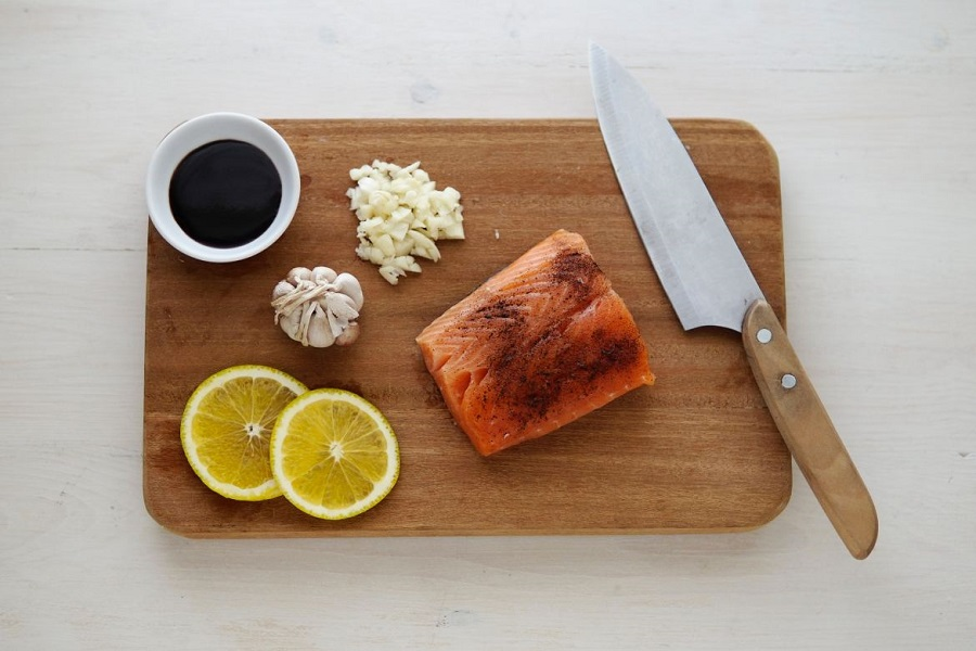 Wooden cutting board with butcher's knife, salmon, lemon, garlic and soy sauce