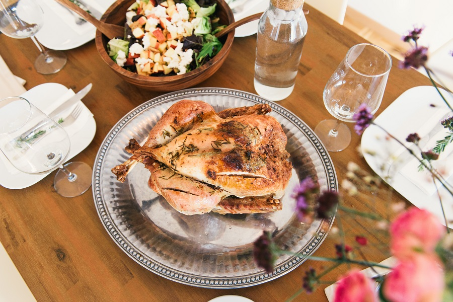 Turkey on a silver platter next to a wooden salad bowl