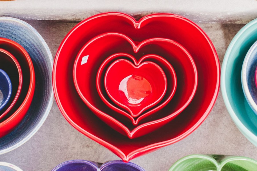 Four red, heart-shaped ceramic bowls nested into one another