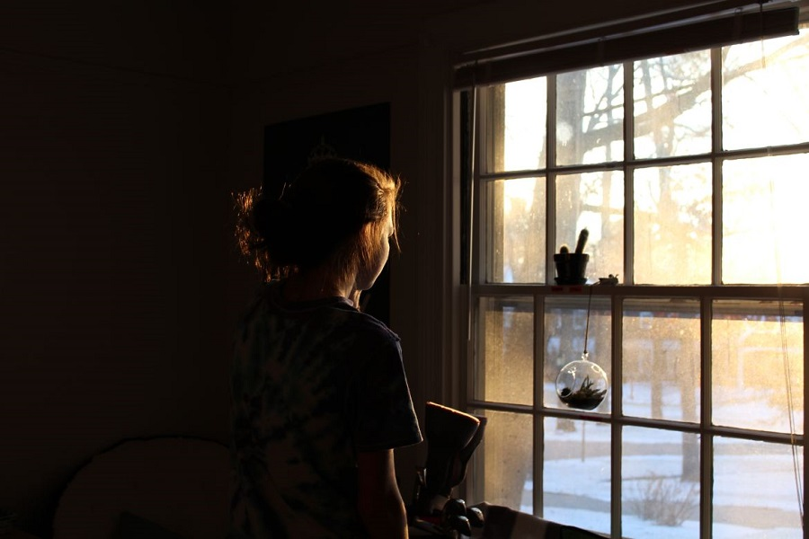 Girl standing in the dark looking out the window with sun streaming in