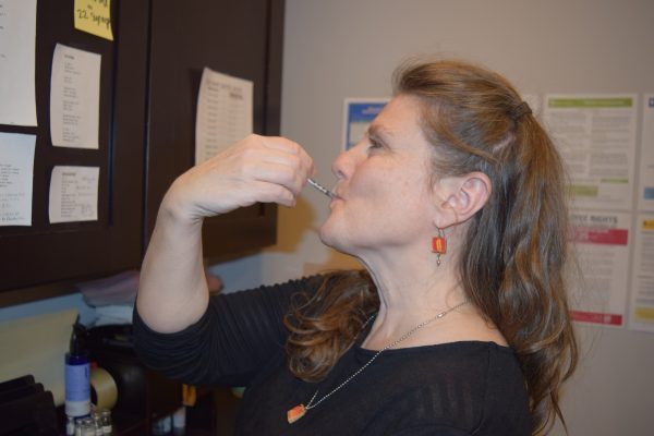 Woman putting syringe in her mouth for immunology treatment