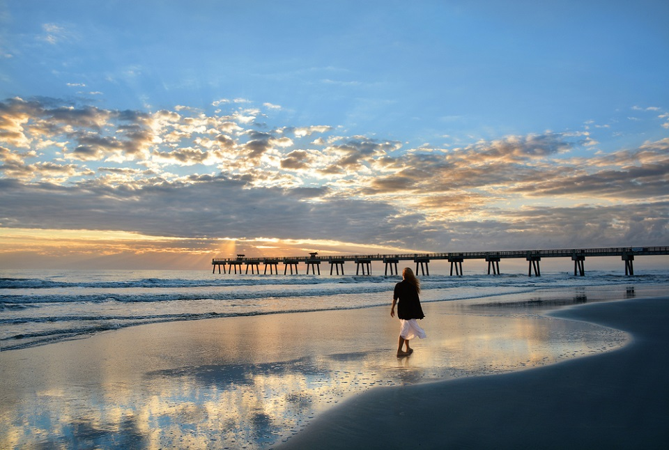 Woman walking along the beach at sunset