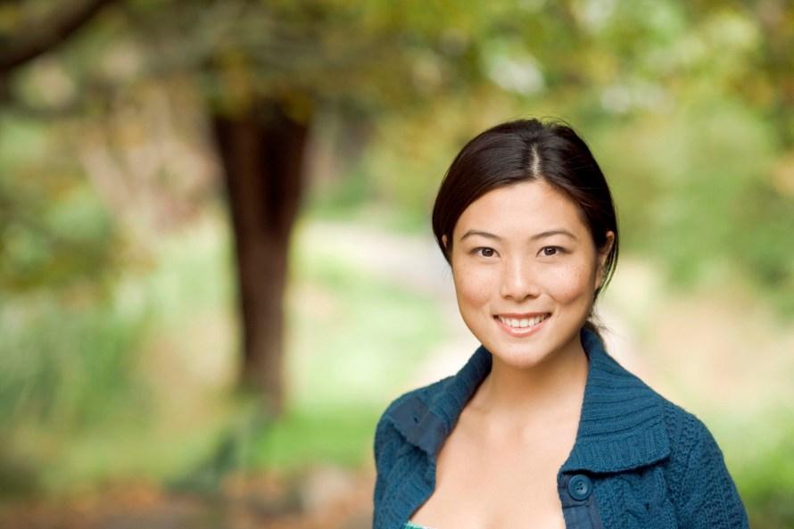 Asian woman smiling outdoors bokeh