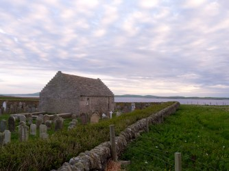 St Boniface Kirk at sunset with Westray in the distance