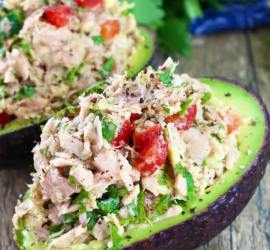 half an avocado with tuna and tomato on top