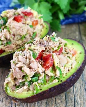 half an avocado with tuna and tomato on top