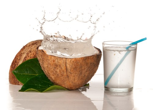 a coconut split in half with a glass of coconut water and a straw