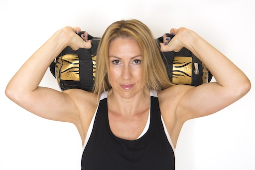 female holding a weight bag across her shoulders